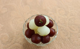 Rasgulla and gulab jamun. Indian sweets Rasgulla and Gulab jamun lying one over another in a glass bowl Stock Photo