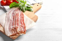 Rashers of bacon on board. Rashers of bacon on wooden board Stock Image