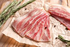 Rashers of bacon on wooden board. Close up Stock Photos