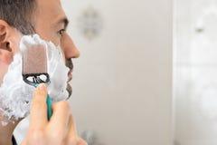 Rasieren des Mannes auf Schaum mit Rasiermesserspiegel im Badezimmer Stockfotos