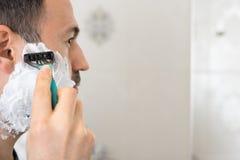 Rasieren des Mannes auf Schaum mit Rasiermesserspiegel im Badezimmer stockbild