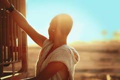 Rasieren-köpfiges Mädchenschattenbild auf der Sonnenunterganglandschaft Stockfotos
