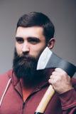 Rasieren mit Axt Porträt des überzeugten jungen bärtigen Mannes, der eine große Axt trägt stockfoto