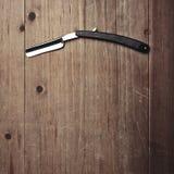 Rasiermesser des Friseursalons auf dem hölzernen Hintergrund Lizenzfreie Stockbilder