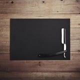 Rasiermesser des Friseursalons mit schwarzem Kraftpapier-Hintergrund Stockbilder