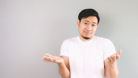 Rasing his shoulder and arms as the decision and choise  is up t. O you. An asian man with white t-shirt and grey background Royalty Free Stock Images
