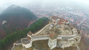 Rasnov Fortress aerial. Rasnov Fortress, in the district of Brasov, Romania , aerial presentation of one side of the  fortress with  defense walls , in  morning stock video