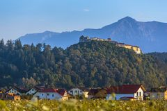 Rasnov fortress and Bucegi mountains, Romania. Autumnal panorama landscape with Rasnov fortified citadel on top of the hill and Bucegi mountains in the morning stock photo