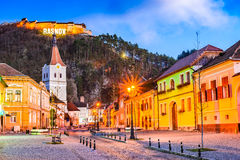 Rasnov, Romania. Evening twilight with medieval saxon city in Transylvania and hilltop ruins of the fortress stock image