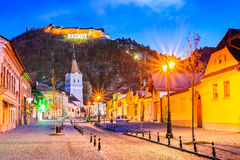Rasnov, Romania. Evening twilight with medieval saxon city in Transylvania and hilltop ruins of the fortress royalty free stock photography