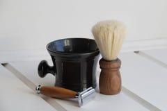 Rasoio marrone di legno, spazzola marrone di legno, ciotola ceramica nera Immagini Stock