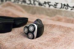 Rasoio rotatorio blu elettrico con tre lame vicino alla cassa ed agli asciugamani di bagno neri immagini stock libere da diritti