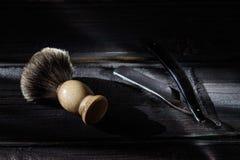 Rasoir droit et brosse de rasage sur un fond en bois de luxe image stock