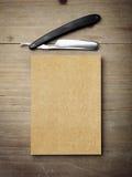 Rasoir droit et papier d'emballage sur le bureau en bois Image libre de droits