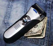 Rasoir et argent sur des jeans Images stock