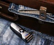 Rasoir et une valise avec des jeans Image stock