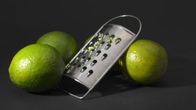 Rasp with lime peel. Kitchen rasp wih lime peel and limes Royalty Free Stock Photography
