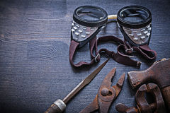 Rasp pliers clamp hammer goggles on vintage board Royalty Free Stock Images