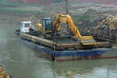 Raspador em uma barca para a limpeza da cama de rio do Rive Fotos de Stock Royalty Free