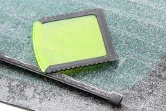 Raspador verde del hielo en la ventana del coche, problemas del invierno en el transporte Imagen de archivo