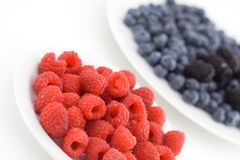 Raspberries. On a plate with blueberries and blackberries in the background stock images