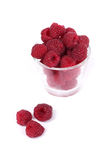 Raspberries. Glass filled with ripe red raspberries isolated on white studio background royalty free stock photography