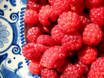 Raspberries. Luscious red raspberries onantique plate Stock Photos