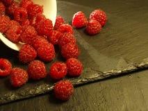 Raspberries. Many raspberries on a black slate background Stock Photo