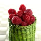 Raspberries. A group of fresh raspberries in a green little basket royalty free stock photo