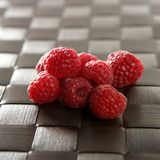 Raspberries. A group of fresh raspberries over brown tablecloth stock image