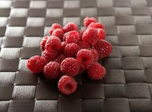 Raspberries. A group of fresh raspberries over brown tablecloth stock images