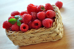 Raspberries in the basket. Fresh raspberries in a basket on a wooden table Royalty Free Stock Photos