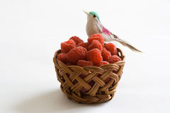 Raspberries in a basket. Raspberries in a handmade basket, toy bird on top Stock Images
