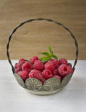 Raspberries in a basket on rustic wooden background Royalty Free Stock Images
