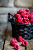Raspberries in a basket on rustic wooden background Stock Photos