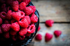Raspberries in a basket on rustic wooden background Royalty Free Stock Image