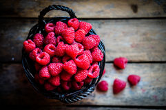 Raspberries in a basket on rustic wooden background Stock Photo