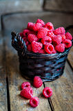 Raspberries in a basket on rustic wooden background Royalty Free Stock Photos