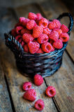 Raspberries in a basket on rustic wooden background Royalty Free Stock Photography