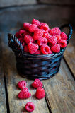 Raspberries in a basket on rustic wooden background Stock Image