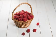 Raspberries in the basket on white background. Raspberries in the basket on white wooden background Royalty Free Stock Photos