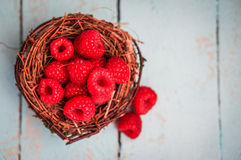 Raspberries in the basket on wooden background Royalty Free Stock Images