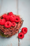 Raspberries in the basket on wooden background Stock Photos