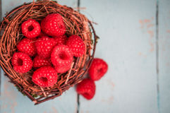 Raspberries in the basket on wooden background Royalty Free Stock Photography
