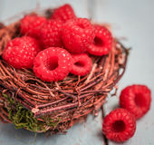Raspberries in the basket on wooden background Royalty Free Stock Photos