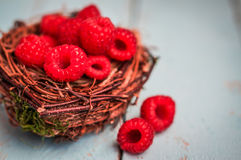Raspberries in the basket on wooden background Stock Photography