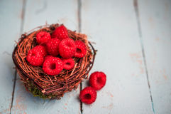 Raspberries in the basket on wooden background Stock Photo