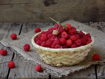 Raspberries in the basket. On wooden background stock image