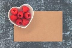 Raspberries in bawl on grunge black background. summer. Fruit royalty free stock photos