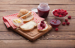 Raspberries berries, raspberries jam, butter and bread on wooden table. Royalty Free Stock Image
